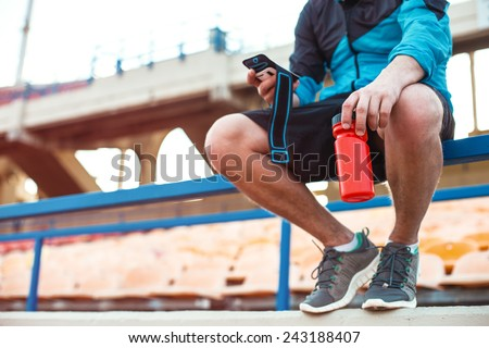 athlete sitting with bottle of water and mobile phone on the railing on the stadium - stock photo