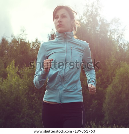 Athlete sportsmen girl running in morning sunrise training for marathon and fitness. Healthy active lifestyle woman exercising outdoors. - stock photo