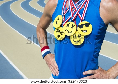 Athlete standing at running track wearing gold medals with bright yellow emoji faces - stock photo