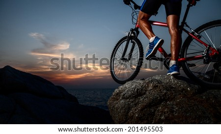 Athlete standing on the rock with bicycle - stock photo