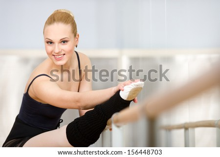 Athlete stretches herself near barre and mirrors in the classroom - stock photo