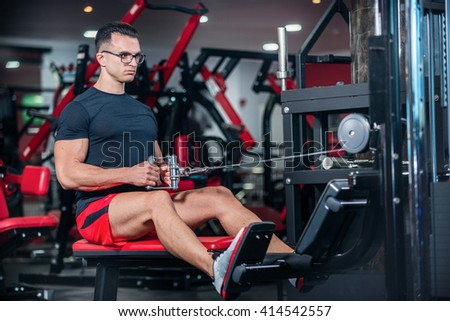 Athlete stretching involved. Strong athlete doing exercise at the gym. The athlete does a workout at the sports simulator. - stock photo
