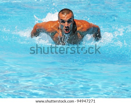 Athlete swimmer training hard in a swimming pool - stock photo