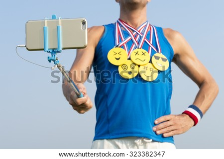 Athlete taking selfie wearing gold medals with bright yellow emoji faces with smartphone on selfie stick - stock photo