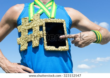 Athlete using tablet hanging next to hashtag gold medal against blue sky - stock photo