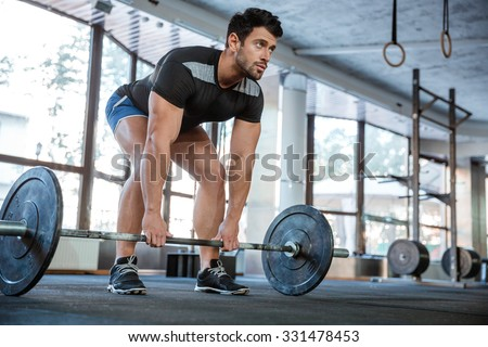Athlete wearing blue shorts and black t-shirt lifting big barbell - stock photo