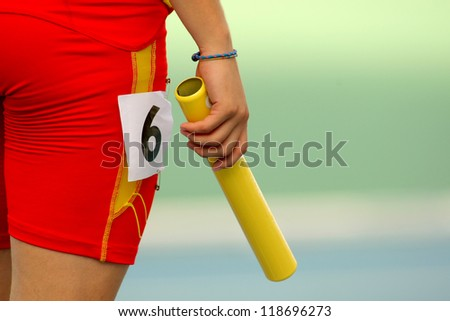 Athlete with a baton waiting for a relay event - stock photo