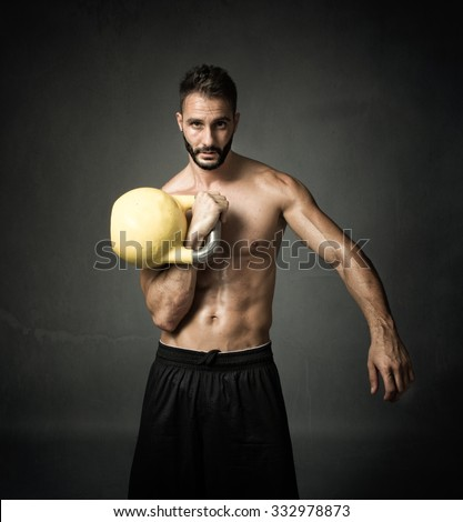 athlete with kettleball, portrait in dark background - stock photo