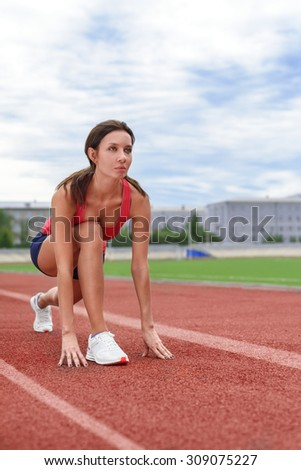 Athlete woman on the starting line. Cloudy weather - stock photo