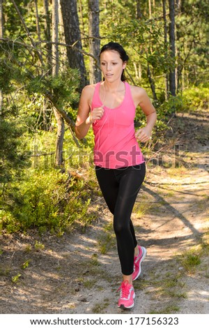 Athlete woman running through forest training in the countryside - stock photo
