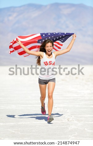 Athlete woman with american flag running with USA t-shirt showing winning gesture excited and happy outdoor in desert nature. Cheerful fitness woman winner cheering. - stock photo