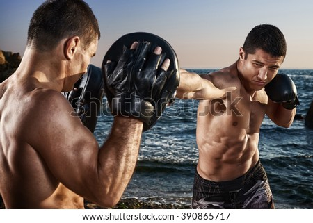 Athlete working on his boxing skills by the sea - stock photo