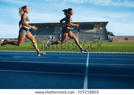 Athletes arrives at finish line on racetrack during training session. Young females competing in a track event. Running race practicing in athletics stadium. - stock photo