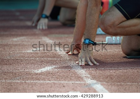 Athletes at the sprint start line in track and field.Hands on the starting line - stock photo
