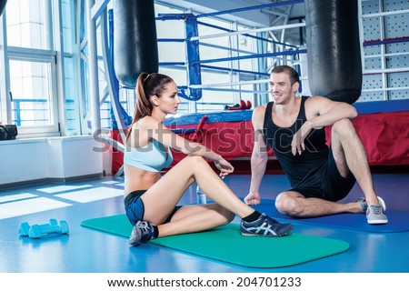 Athletes in sportswear sit on the floor and talking ringside boxing - stock photo