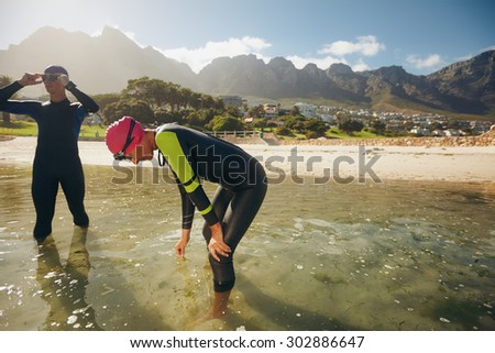 Athletes resting after triathlon training session. Young man and woman standing in water taking a break from practicing. - stock photo