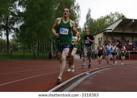 athletes running along the track - stock photo