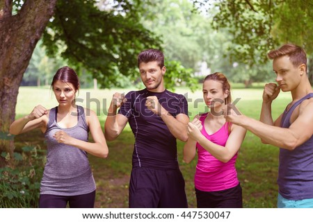 Athletes stand together in a fighting stance with fists at the ready while out on a forest clearing in - stock photo
