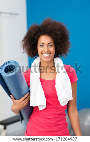 Athletic African American woman arriving at the gym with her aerobics mat under her arm pausing to give the camera a lovely friendly smile - stock photo