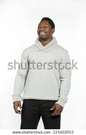 Athletic and attractive black male wearing a fitted gray sweater with black pants in a studio setting on a white background posing and laughing at the camera. - stock photo