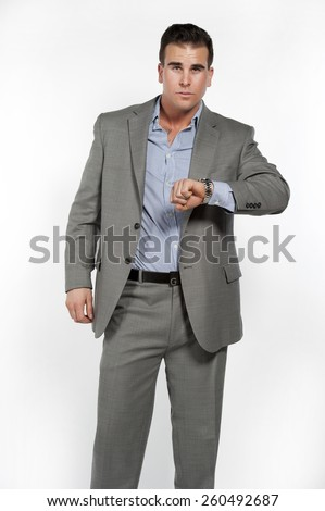 Athletic and attractive caucasian male wearing a fitted gray suit with a blue button down shirt in a studio setting on a white background posing and looking at the camera and his watch. - stock photo