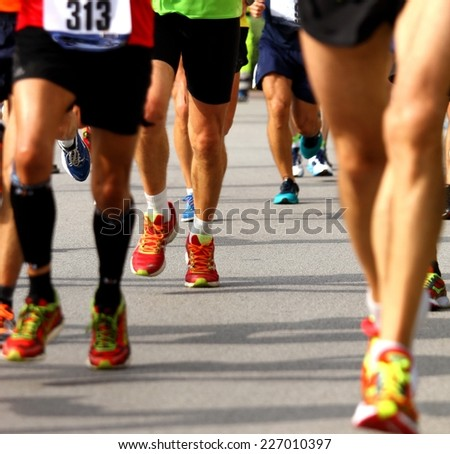 athletic and muscular legs of athletes during the race - stock photo