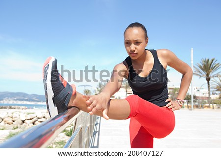 Athletic and sporty young african american black woman stretching her legs and body while exercising on a sunny day against a bright blue sky. Sport active lifestyle outdoors. - stock photo