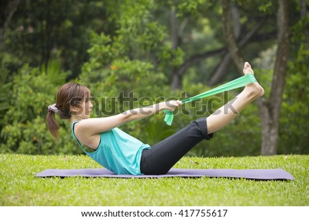 Athletic Asian woman exercising with a resistance band. Action and healthy lifestyle concept. - stock photo