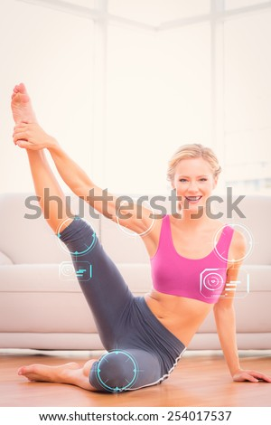 Athletic blonde sitting on floor stretching leg up smiling at camera against fitness interface - stock photo