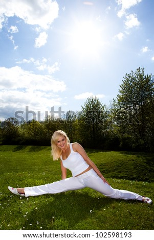 Athletic blonde woman dressed in a fresh white outfit stretching and doing the splits with her legs on a green lawn in a fitness concept - stock photo