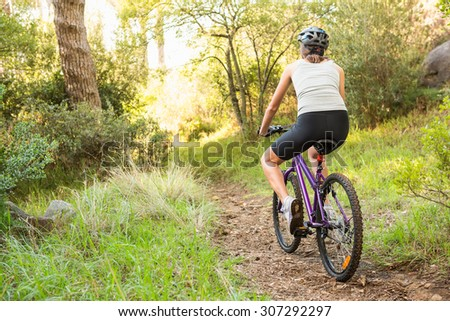 Athletic brunette mountain biking on path in the nature - stock photo
