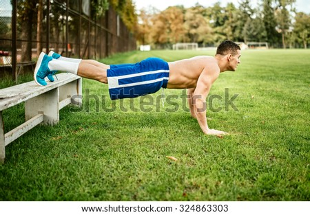athletic built man doing pushups and core training in park. Fitness basketball player training on grass - stock photo
