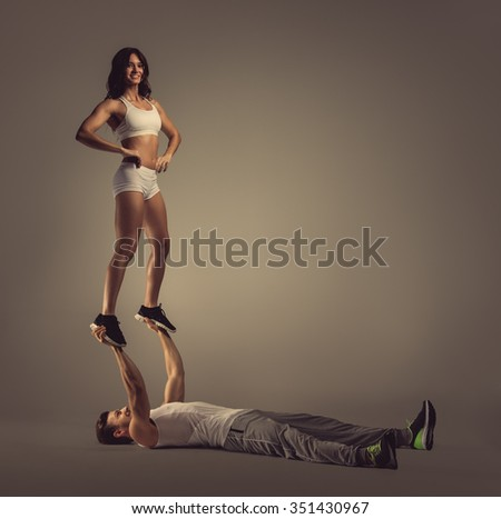 Athletic couple doing acro yoga, studio shot - stock photo