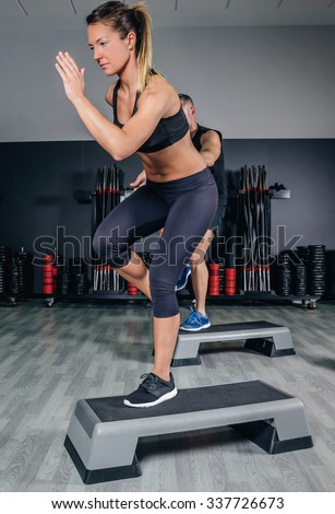 Athletic couple doing exercises over steps in aerobic class on a fitness center. Sport and health concept. - stock photo