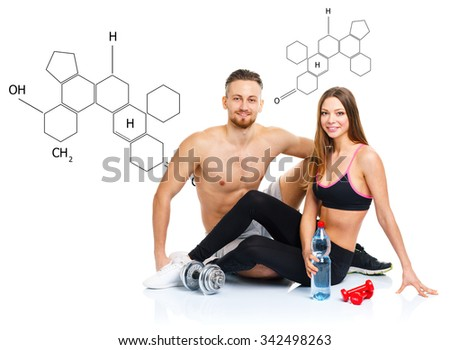 Athletic couple - man and woman after fitness exercise sitting with dumbbells on the white with the chemical formula on background - concept of healthy life - stock photo
