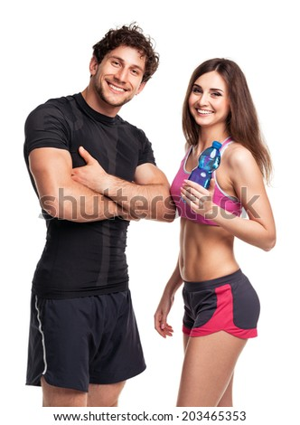 Athletic couple - man and woman with bottle of water on the white background - stock photo