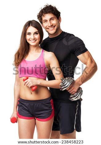 Athletic couple - man and woman with dumbbells on the white background - stock photo