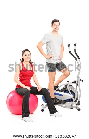 Athletic couple posing with a fitness equipment, cross trainer machine and pilates ball, isolated on white background - stock photo