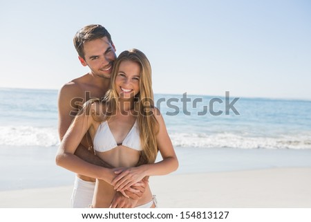 Athletic couple smiling at camera at the beach - stock photo
