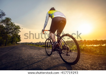 Athletic cyclist on the road in a beautiful area in the afternoo - stock photo
