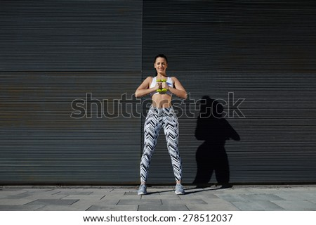 Athletic female holding weights dumbbells with her hands together, young woman in sporty clothing training bicep curls outdoors standing against background with copy space for text message by sides - stock photo