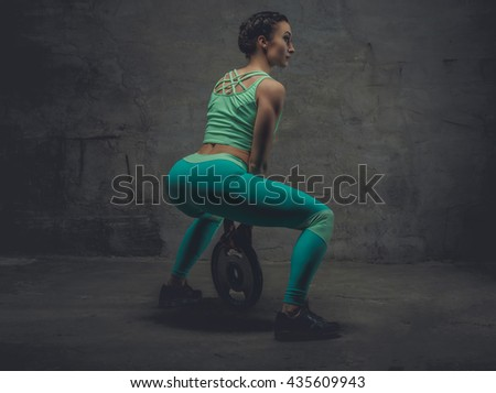 Athletic female in a zure sportswear doing squats. - stock photo