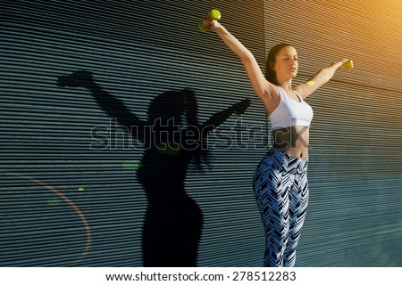 Athletic female with perfect figure getting her arms in great shape while lifting weights, attractive young woman using dumbbells to work out her arms while training outdoors on copy space background - stock photo