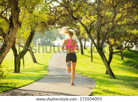Athletic fit young woman jogging running outdoors early morning in park. Healthy lifestyle sports fitness concept. - stock photo