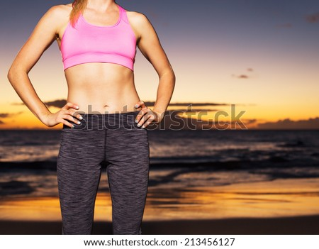 Athletic fitness woman at sunset. Strong toned sexy body. - stock photo