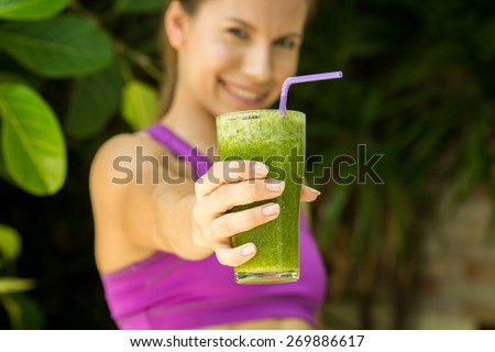 Athletic girl holding a green smoothie - stock photo