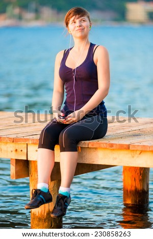 athletic girl with a player on the pier at the sea - stock photo