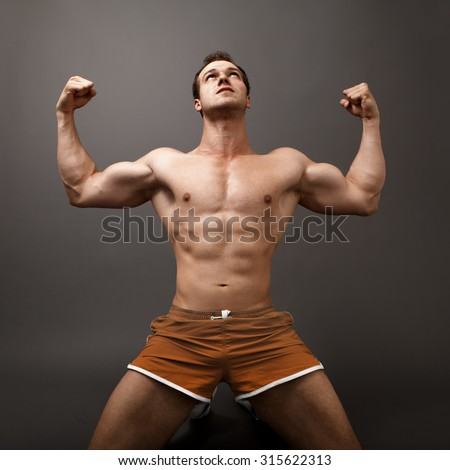 Athletic guy showing his muscles - winner victory concept - stock photo