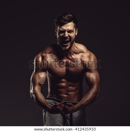 Athletic handsome man showing biceps muscles, studio shot - stock photo