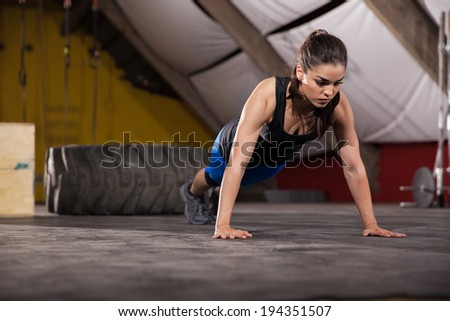 Athletic Latin woman doing push ups with extreme determination in a cross-training gym - stock photo